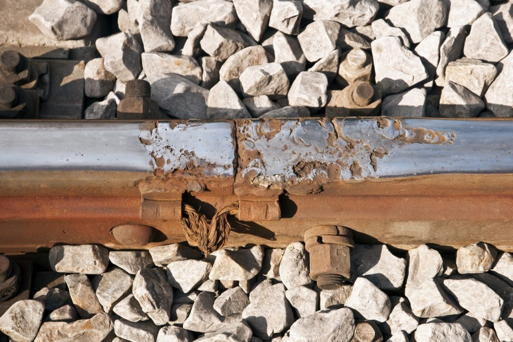 View of damaged metal coating on railroad track
