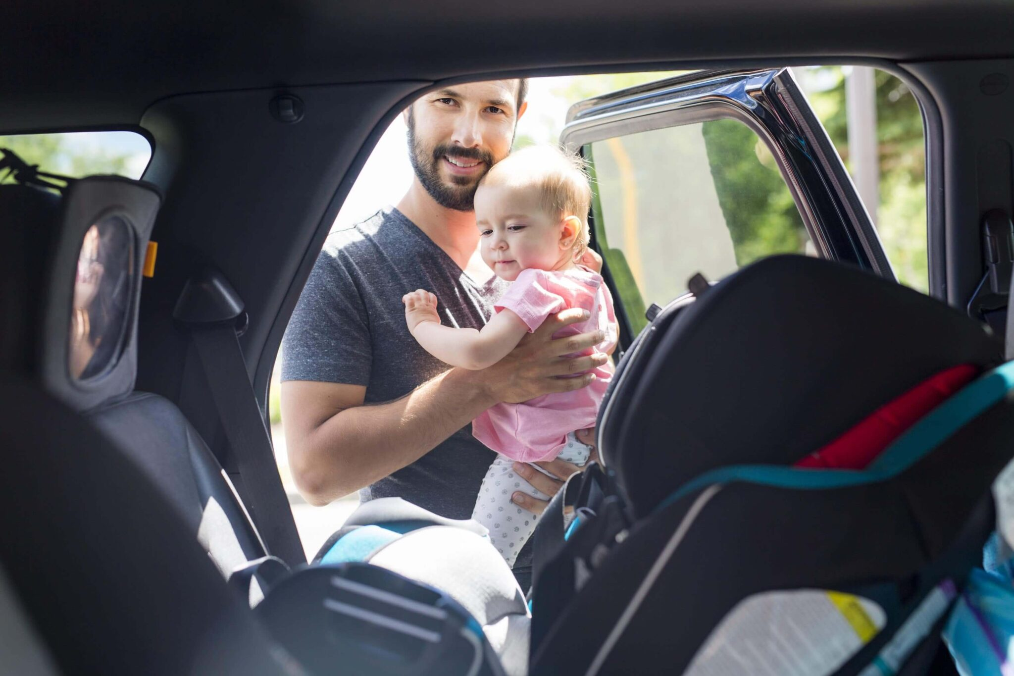 Happy man putting young child in a car seat
