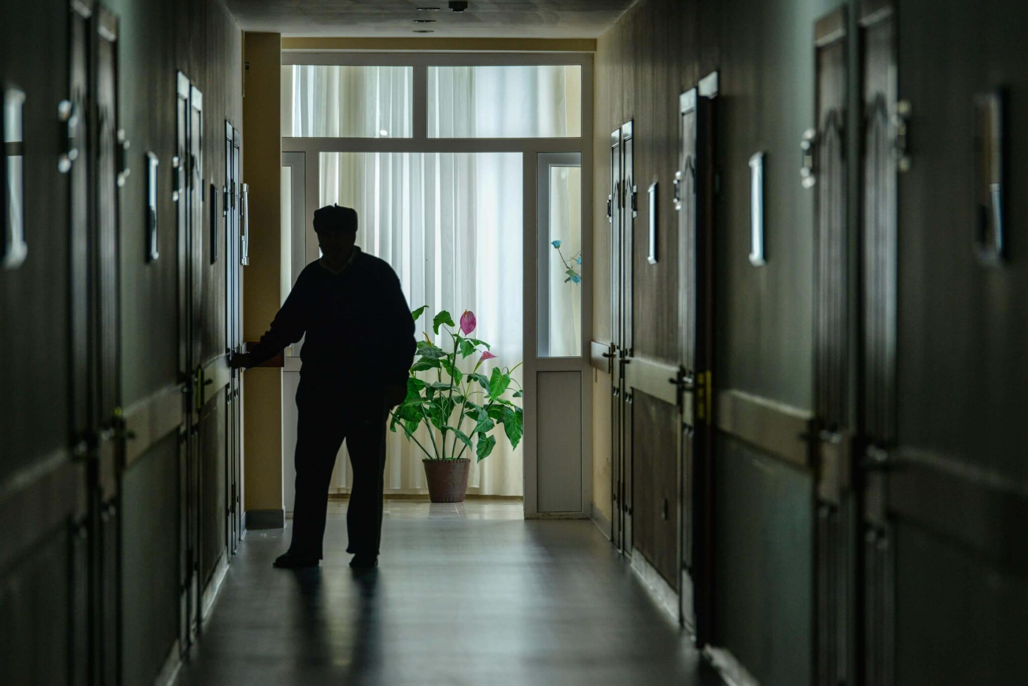 Silhouette of nursing home patient walking down a hallway