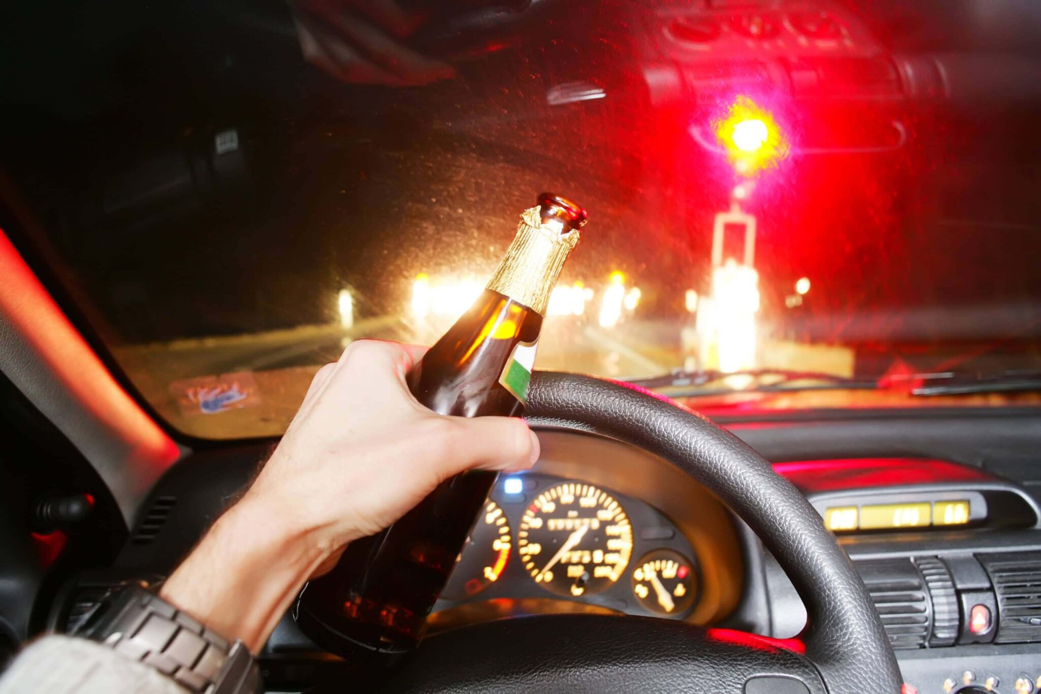 view of a steering wheel with driver's hand on it holding a beer