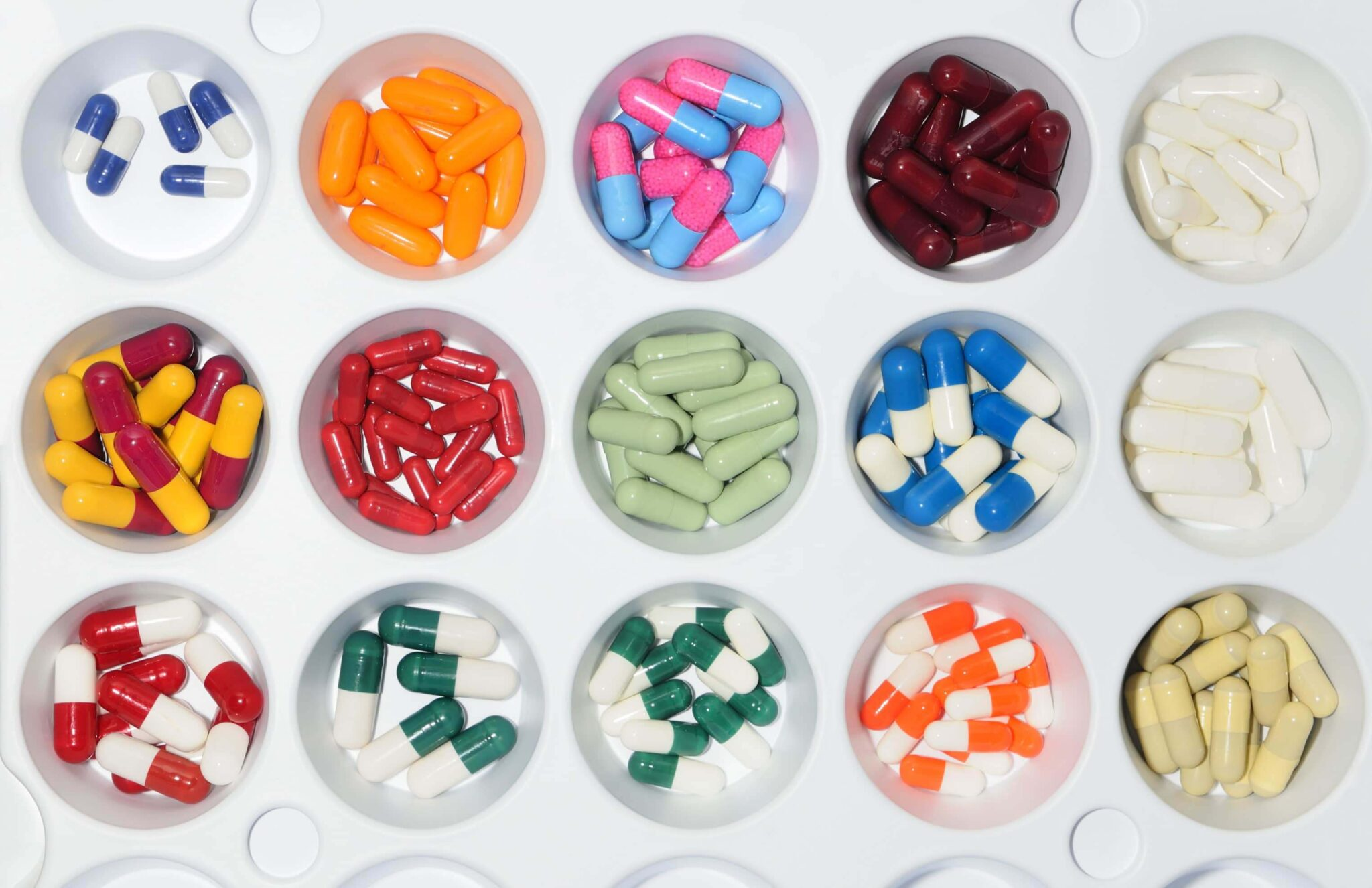 variety of pills displayed in round containers
