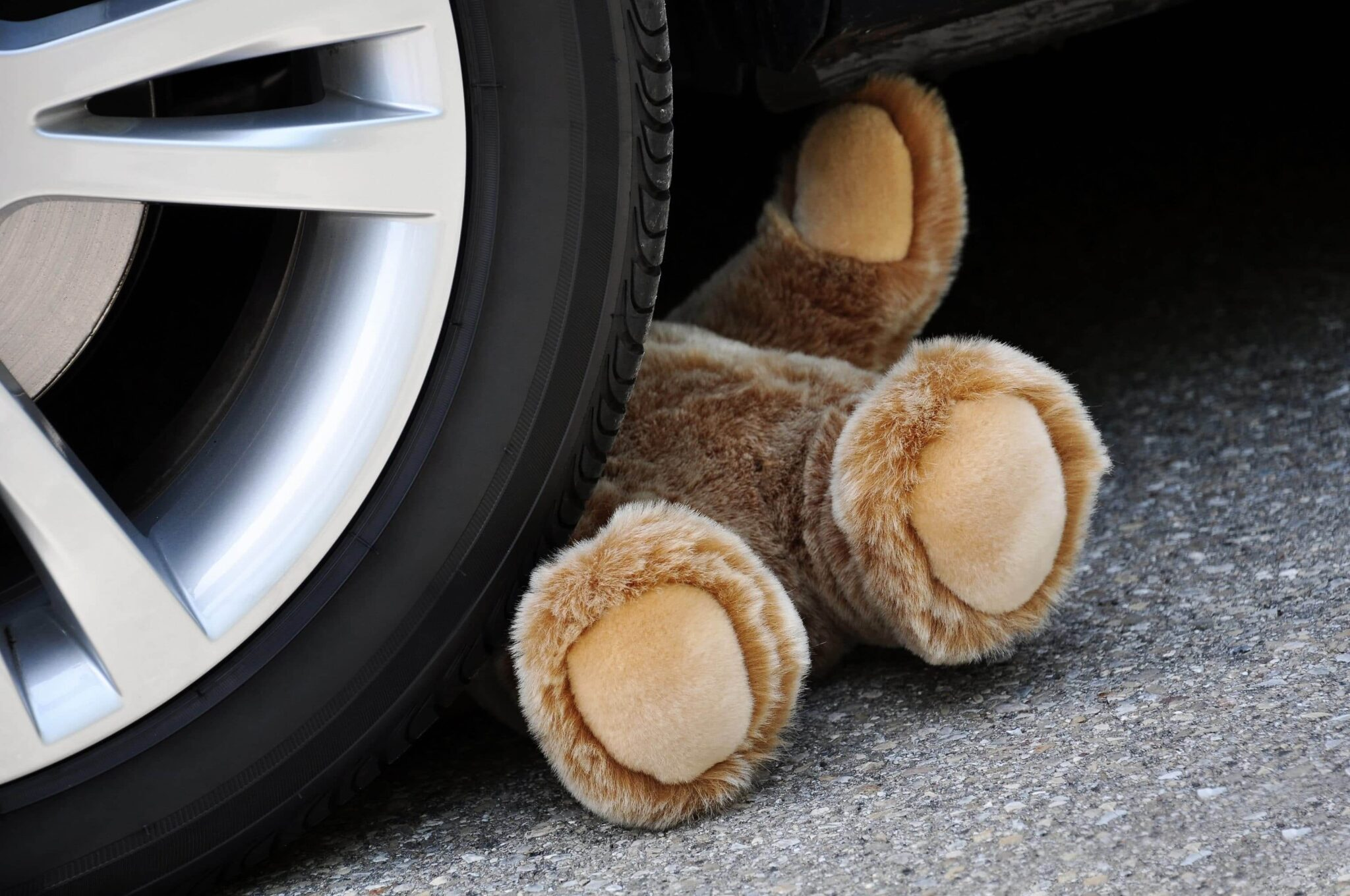 Teddy bear under the wheel of a car