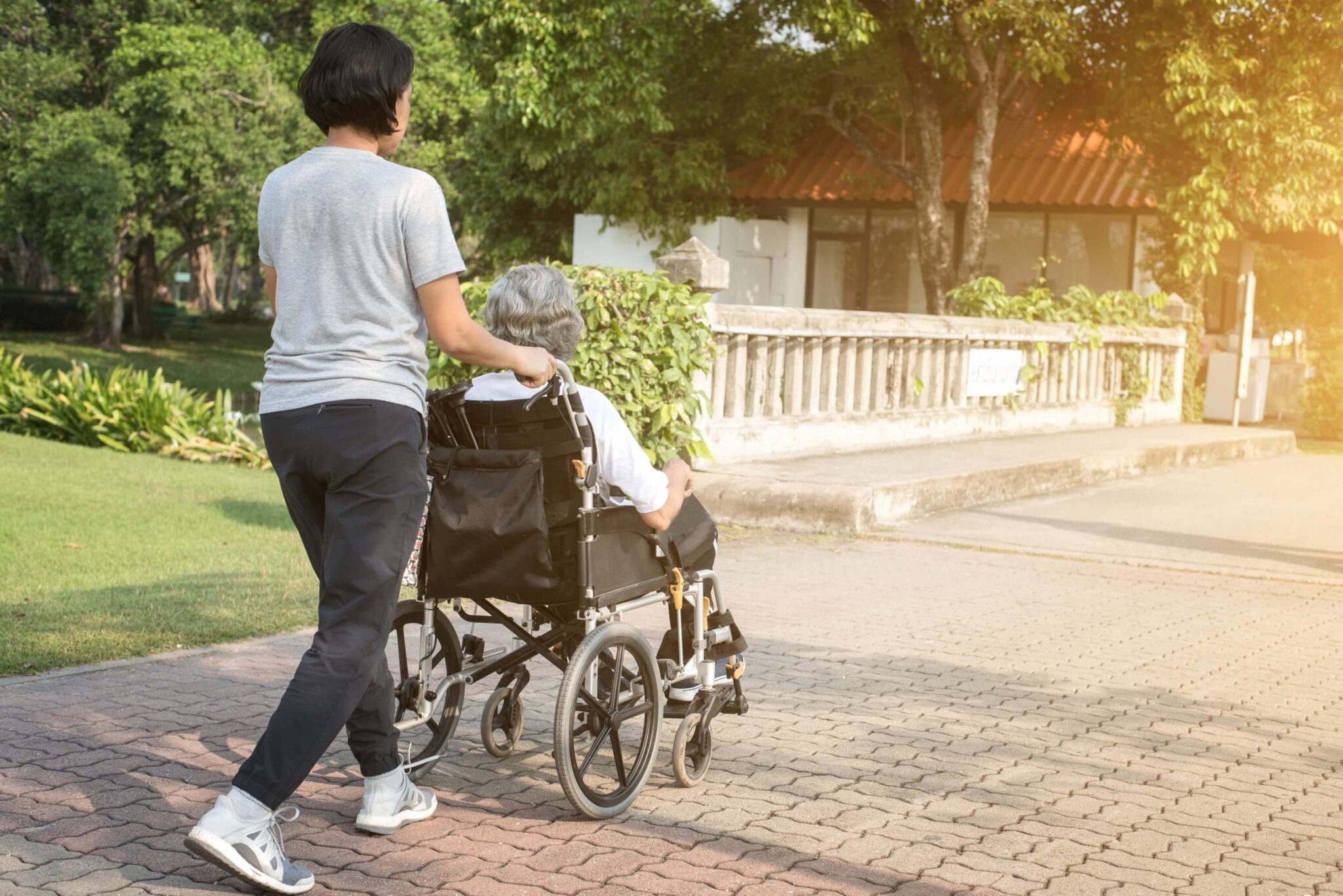 woman pushing another woman in a wheelchair in the summer outside a nursing home