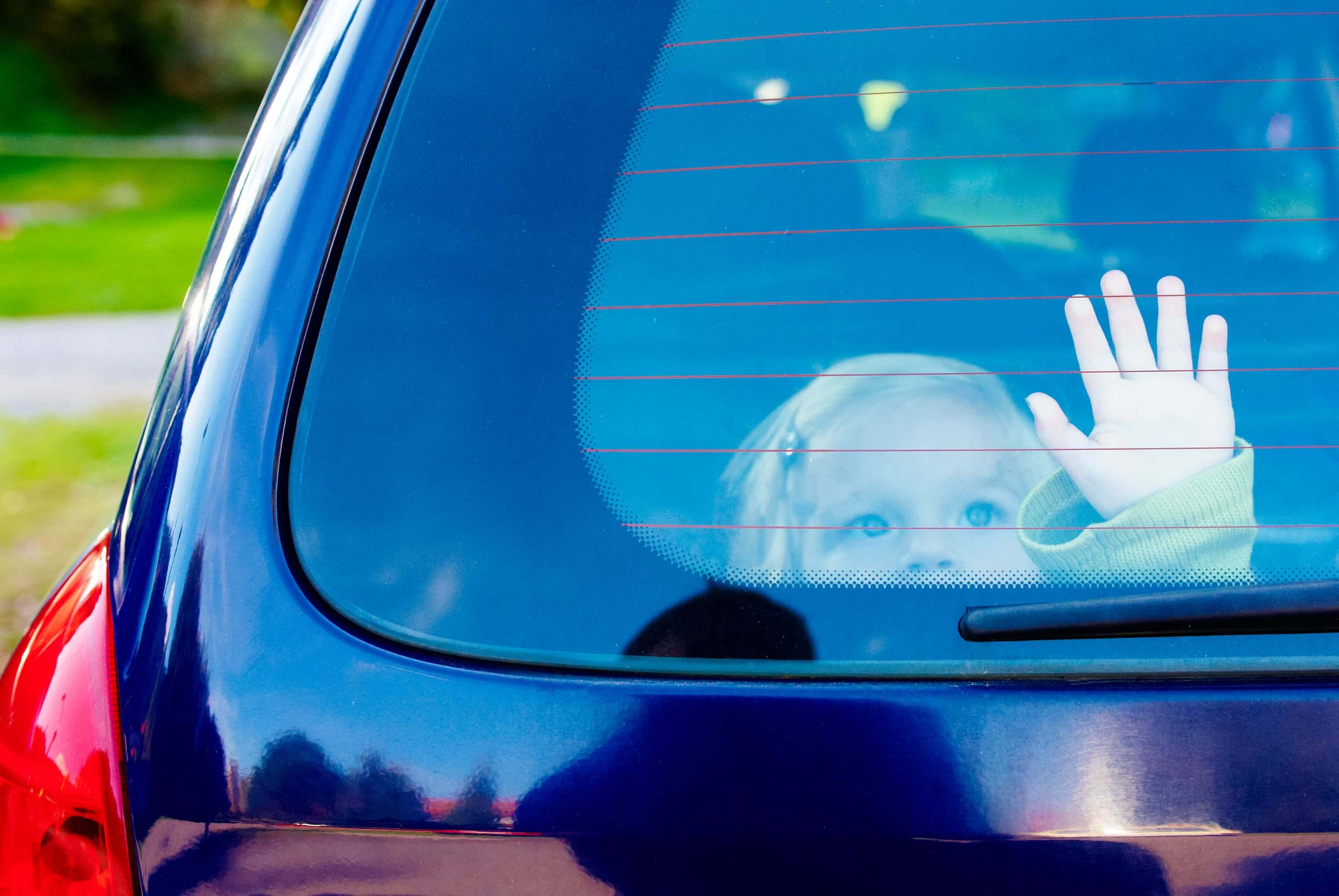 child looking out through rear window in car