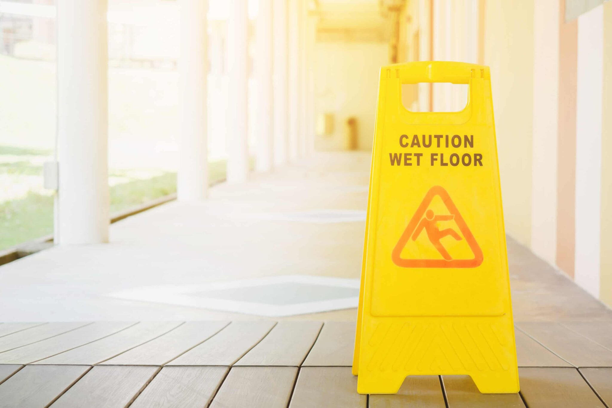Caution Wet Floor sign on porch setting with bright sunny background