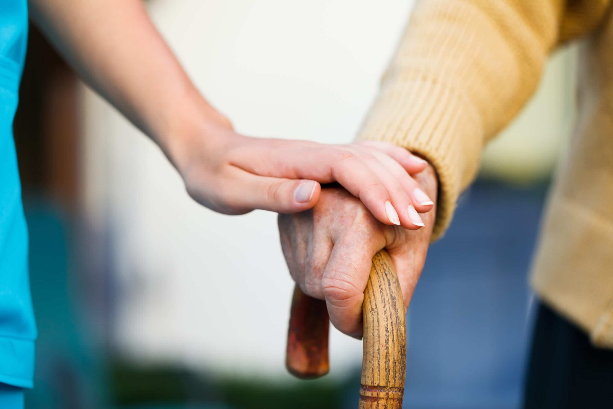 Young person's hand supporting the hand of an older person holding a cane