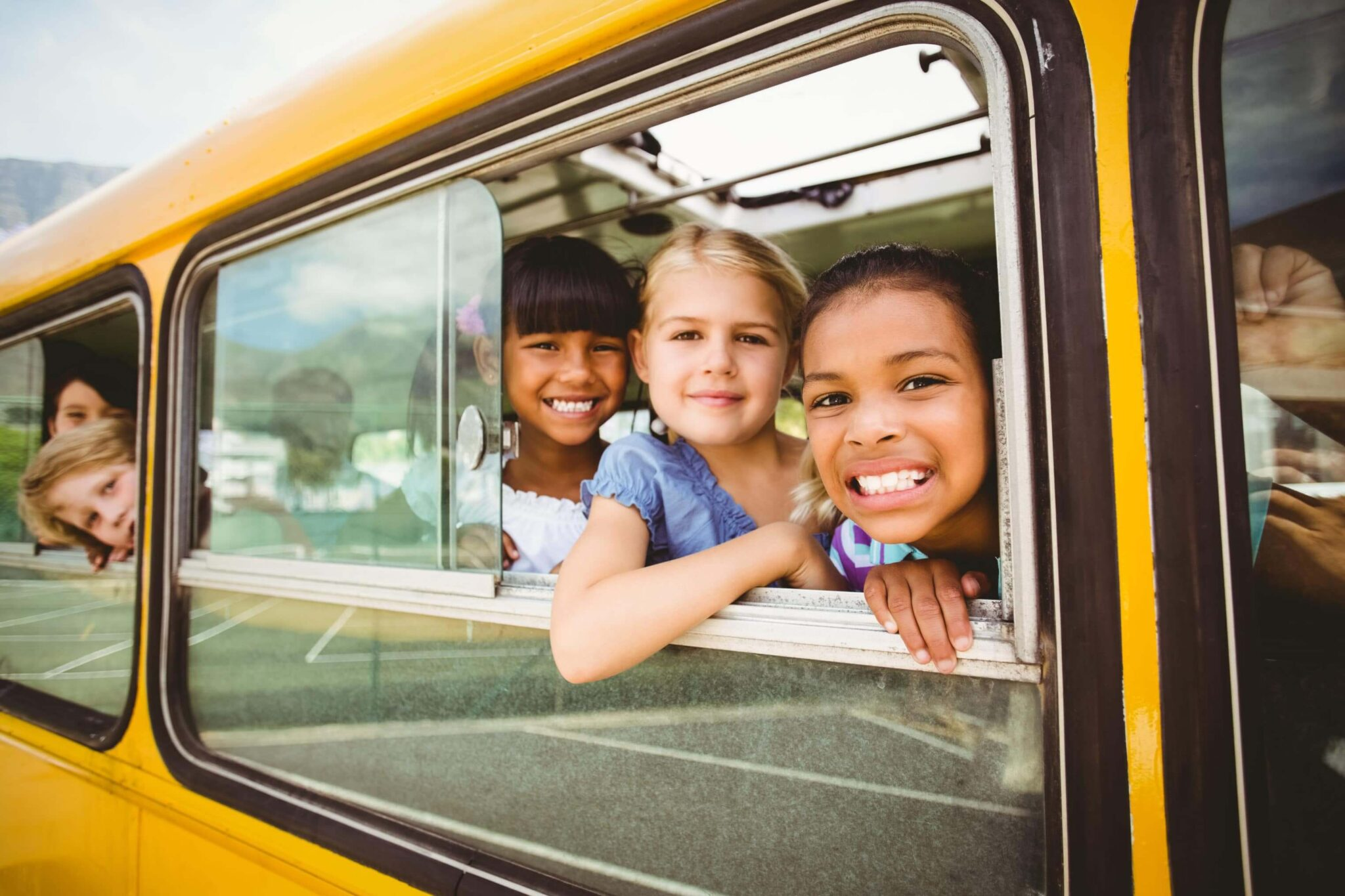 Smiling kids looking out the window on a school bus