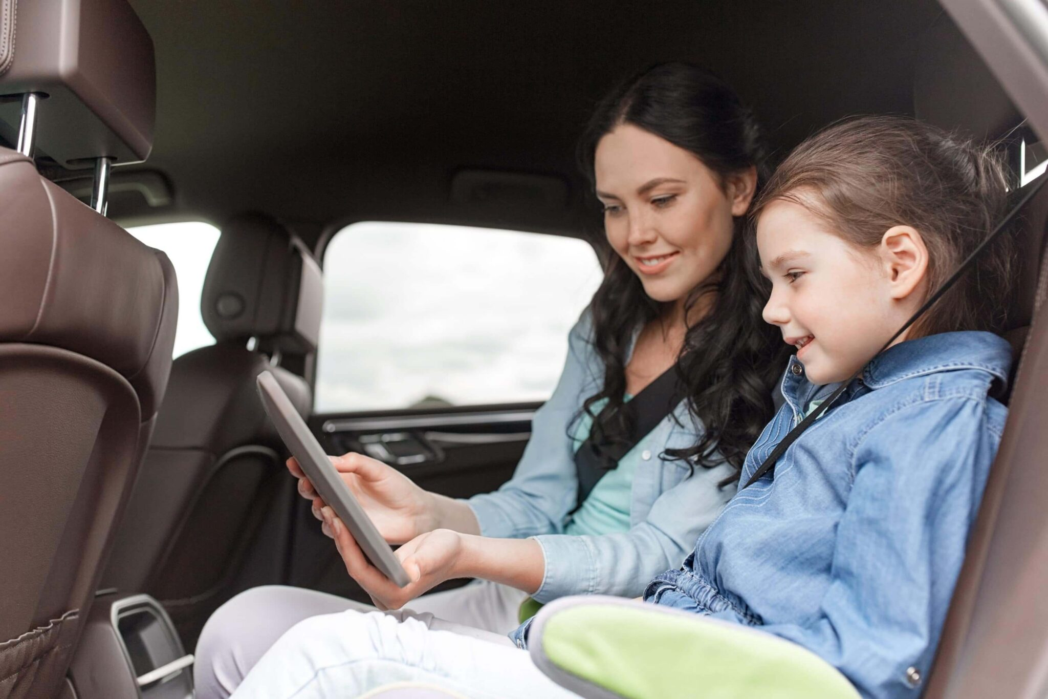 woman holding a table device and showing it to her child in the back seat of a car