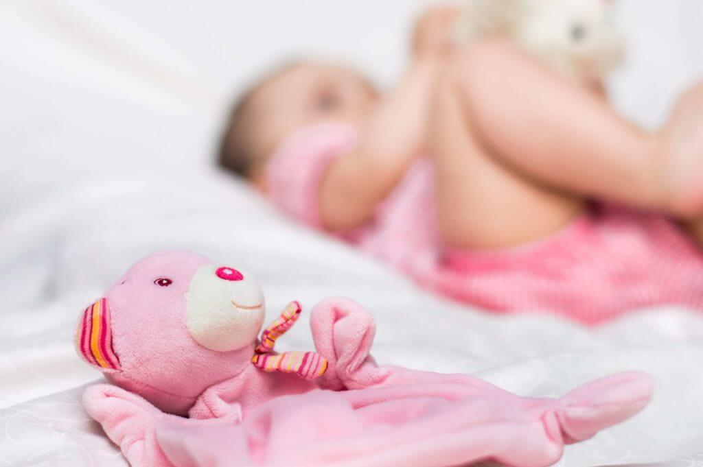 Pink stuffed animal in foreground with baby shown blurred in the background