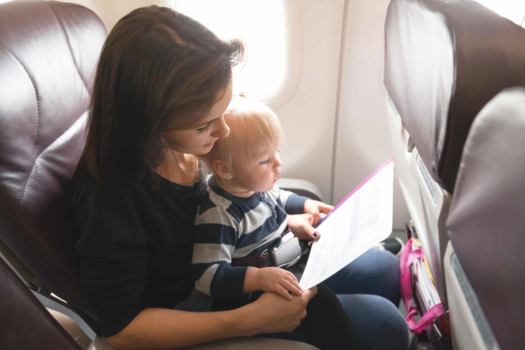 Woman reading to a child on an airplane