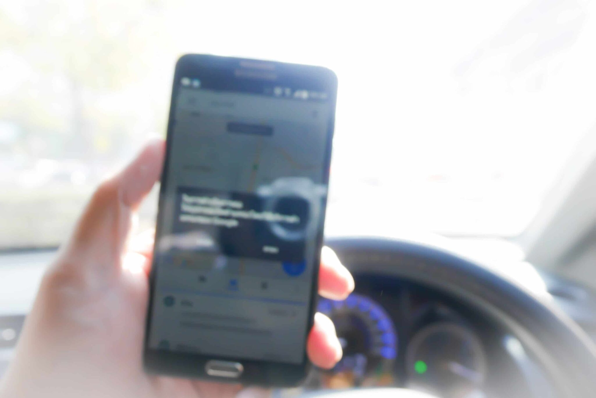 Driver's hand holding phone showing navigation software near the dashboard
