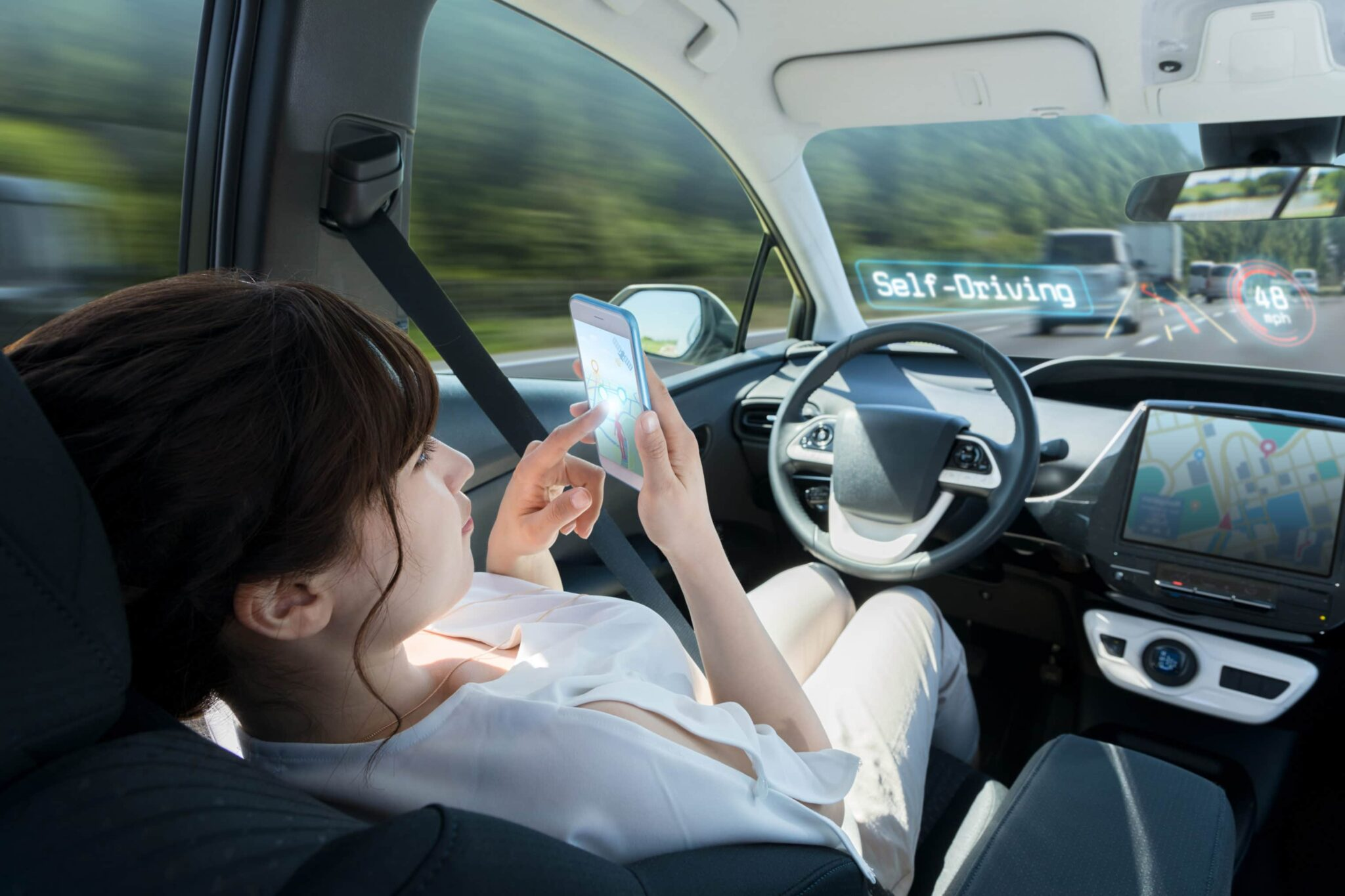 woman relaxing while looking at phone behind the wheel as car drives itself