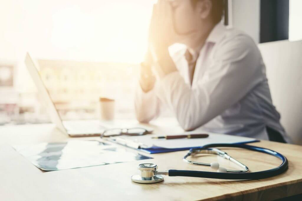 tired physician shown blurred in the background at desk covering face