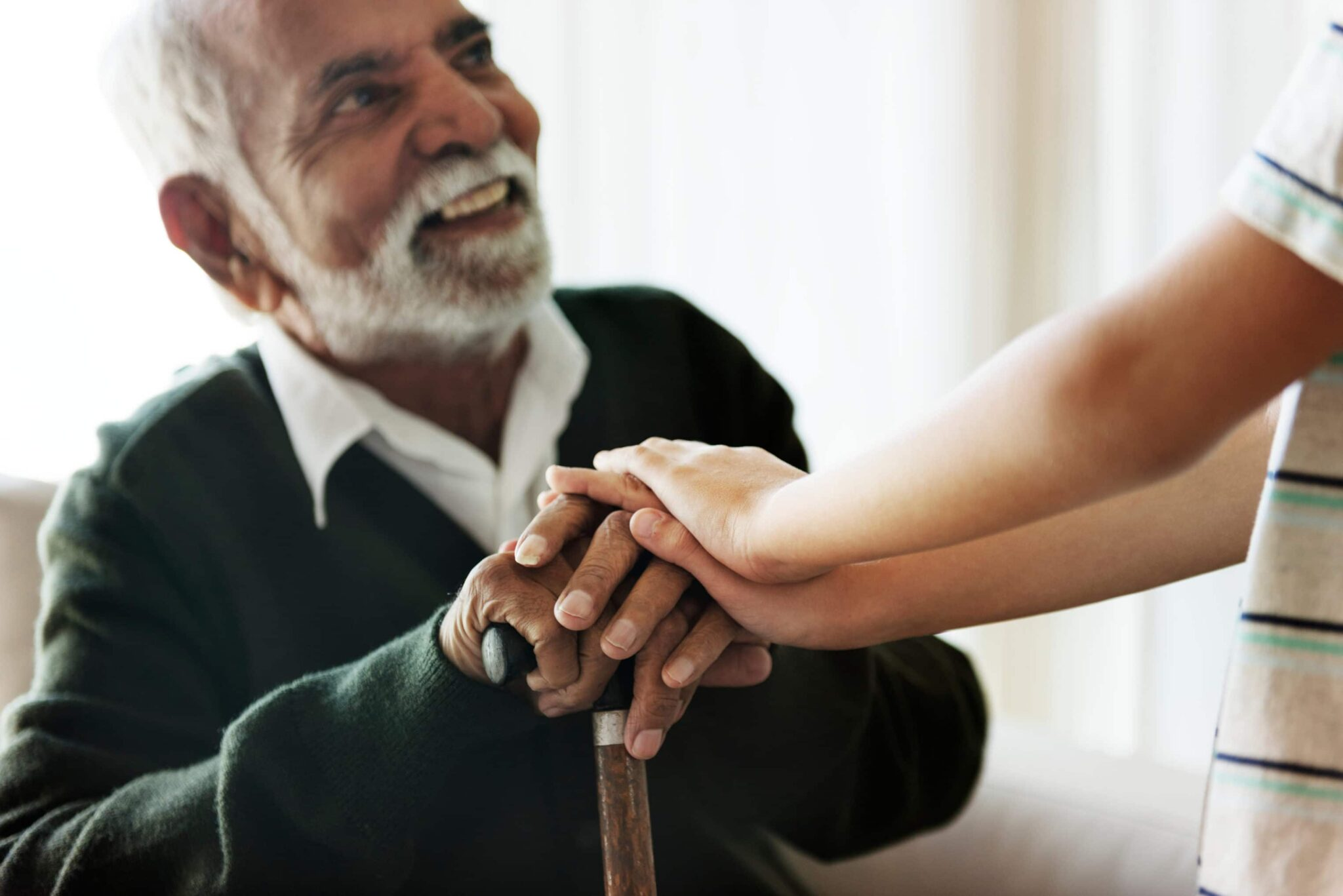Child placing his hands over the hands of an older gentleman holding a cane