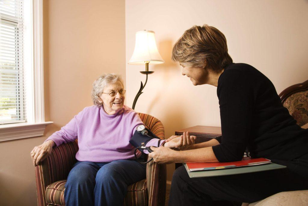 Nursing home caretaker taking the blood pressure of a senior patient