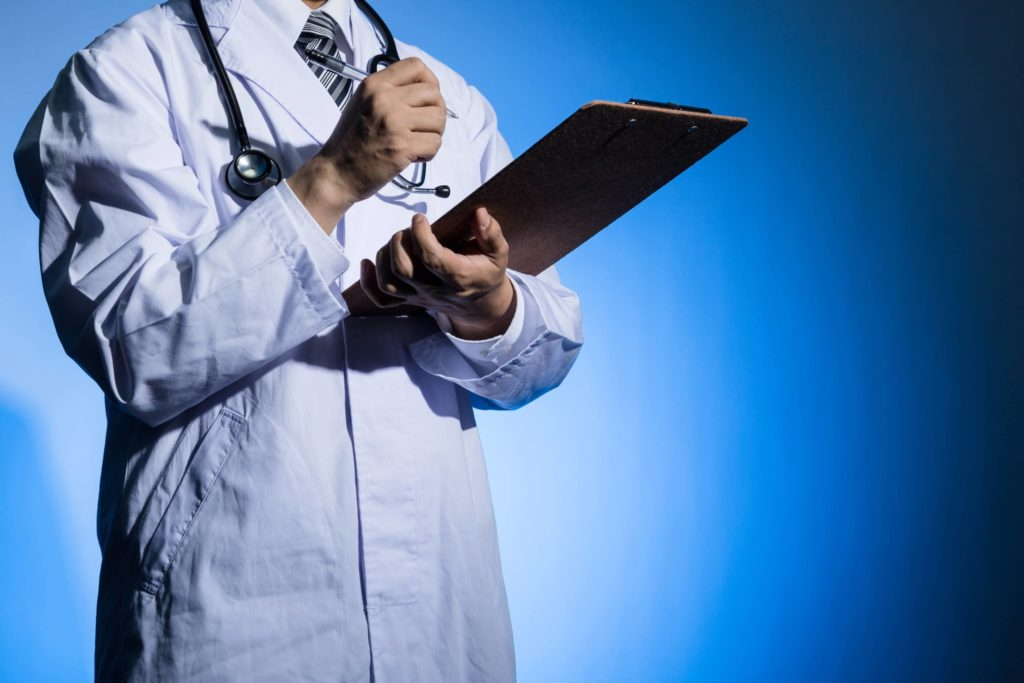 Doctor in a white coat holding clipboard with blue background