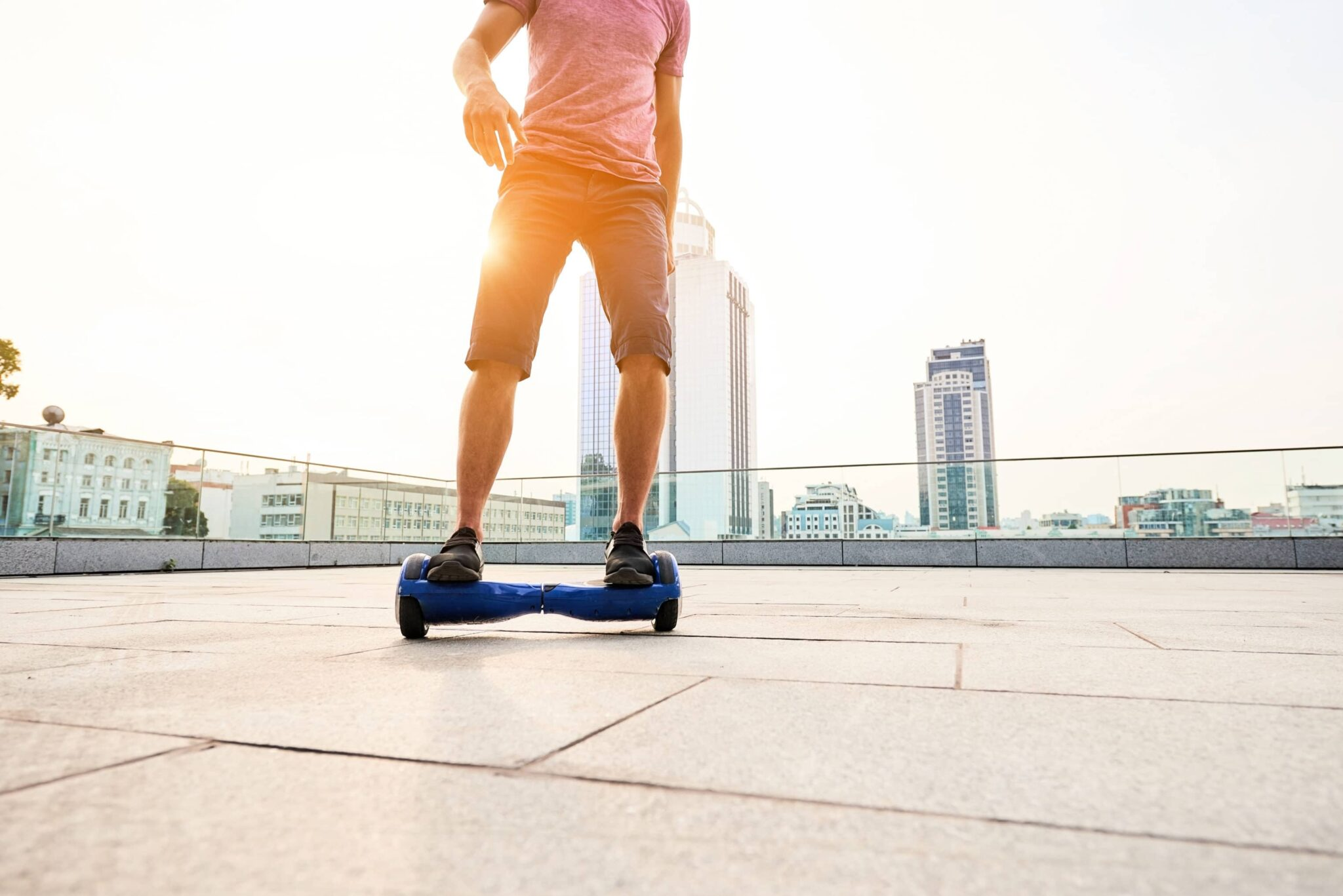 Young man riding on a hoverboard on the roof of a building with high-rise buildings shown in the background
