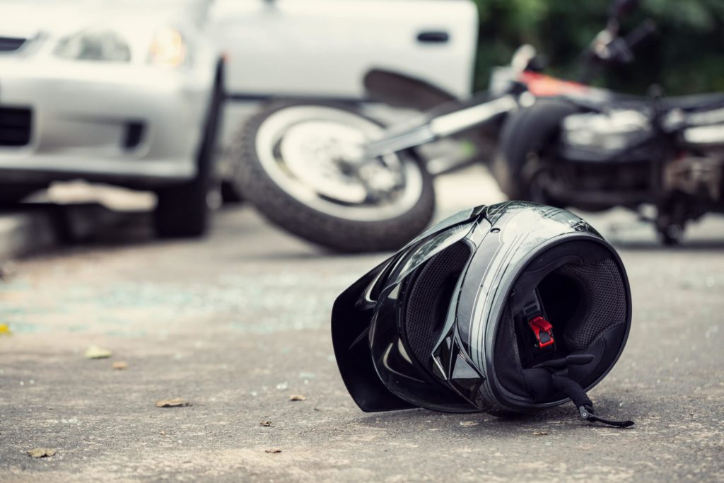 Motorcycle helmet shown in the foreground at the scene of a motorcycle accident with a motor vehicle.