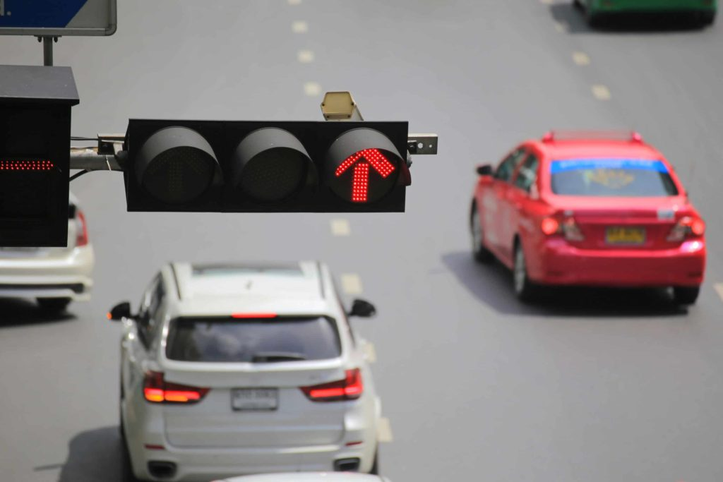 Red light arrow signal in foreground with cars driving below in the background