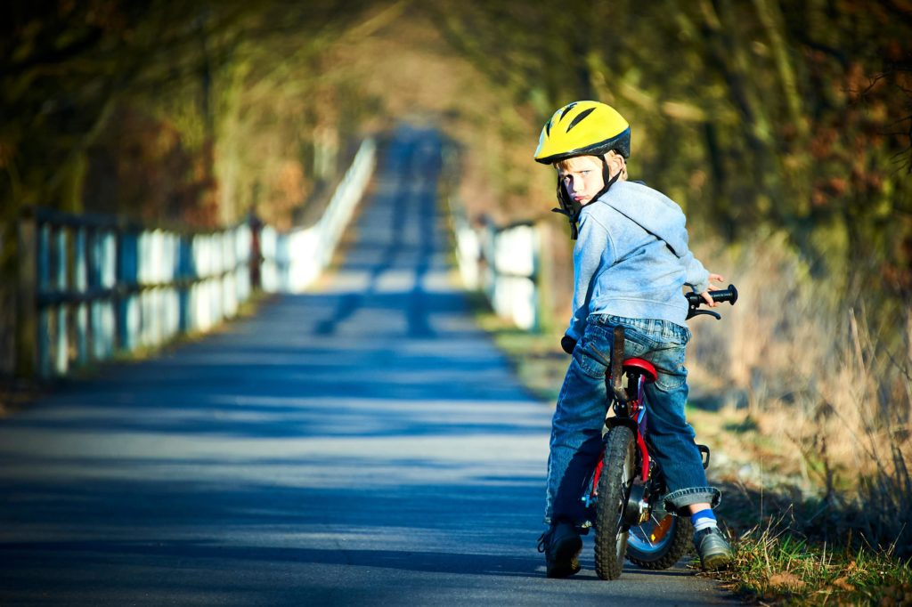 child on a bike looking backward on an open country road