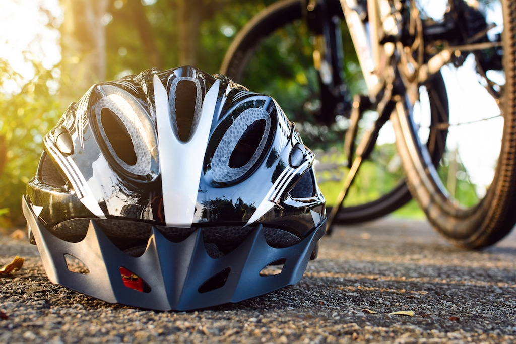 bike helmet in foreground with bicycle in the background and sunshine