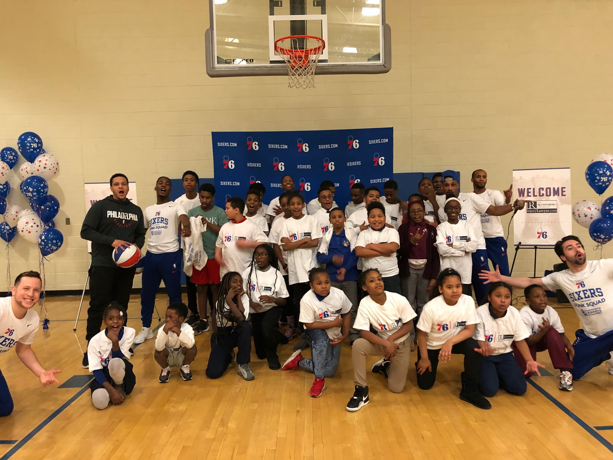 Children from the Chester, PA area pose for a picture under a basketball hoop with Philadelphia 76ers tee-shirts