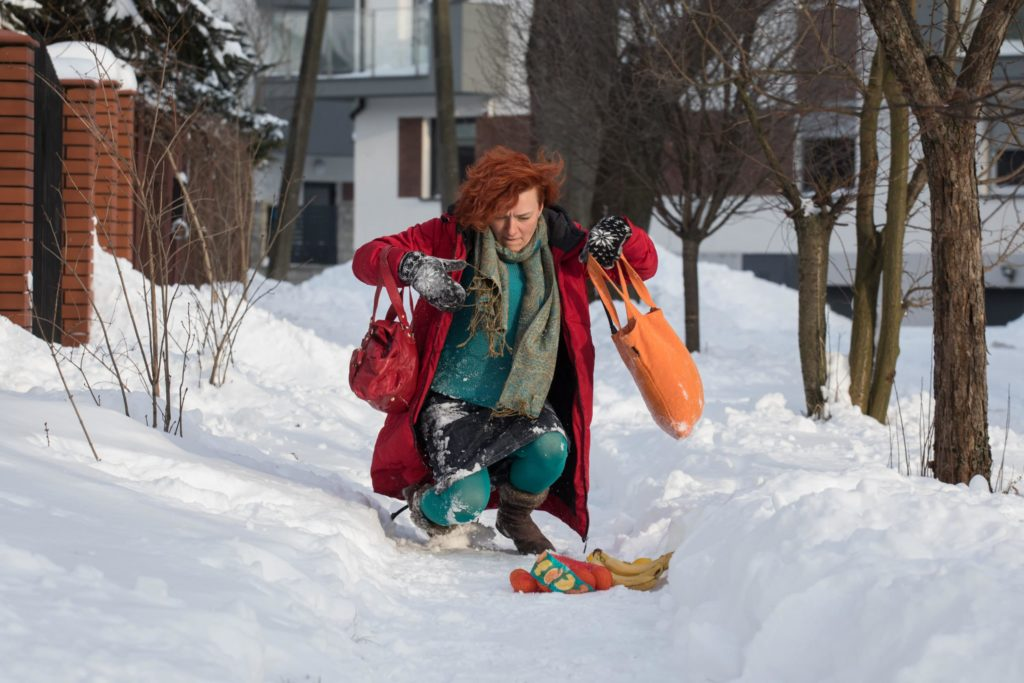 Woman with red hair and blue snow suit mid-fall on a snowy sidewalk