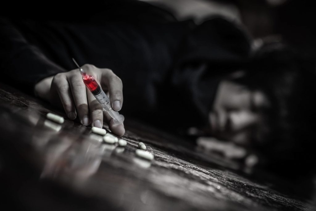 hand of a person laying on the floor holding a syringe with red fluid and surrounded by white pills