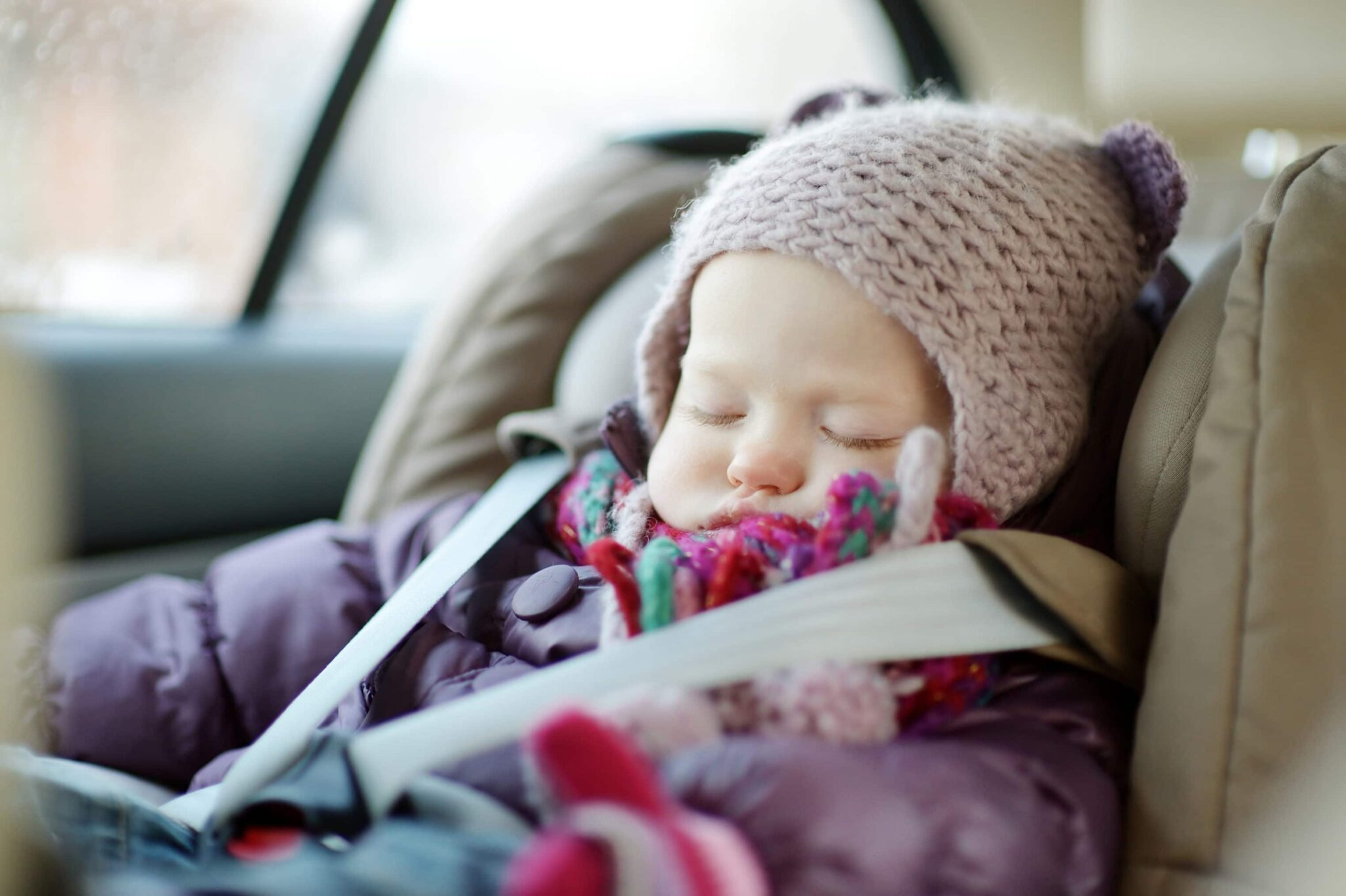 Infant in winter coat and hat in a car seat