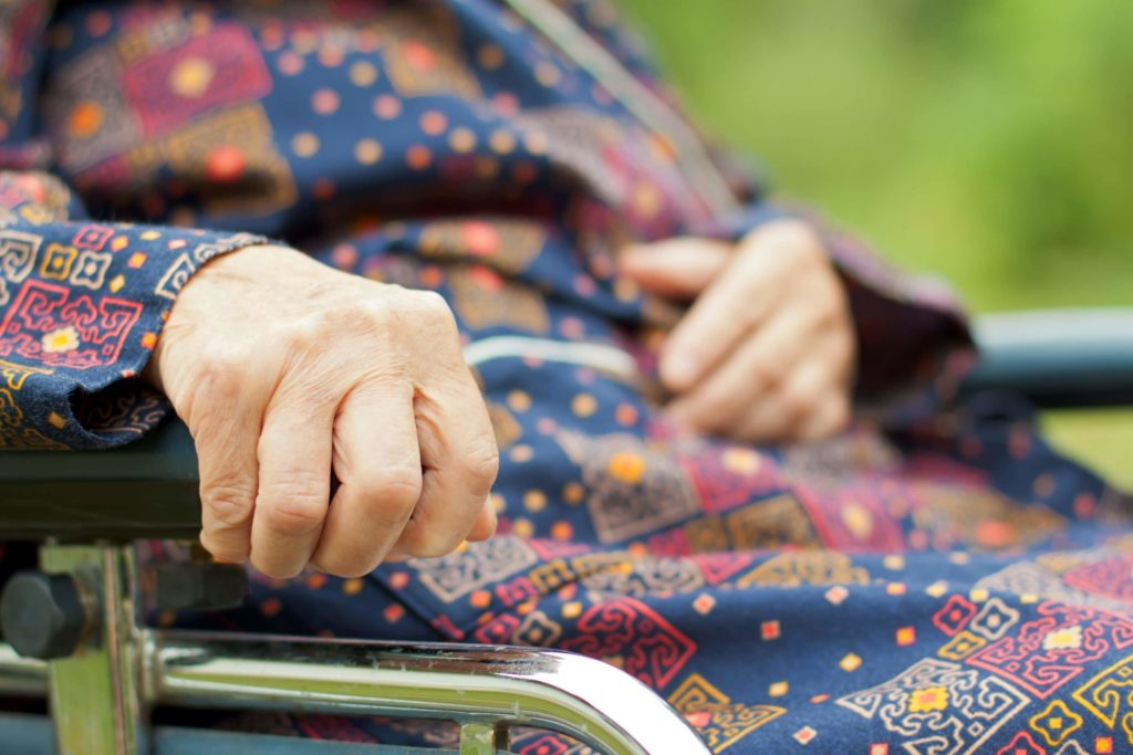 Hand of an older woman grips the arm rest of a wheelchair
