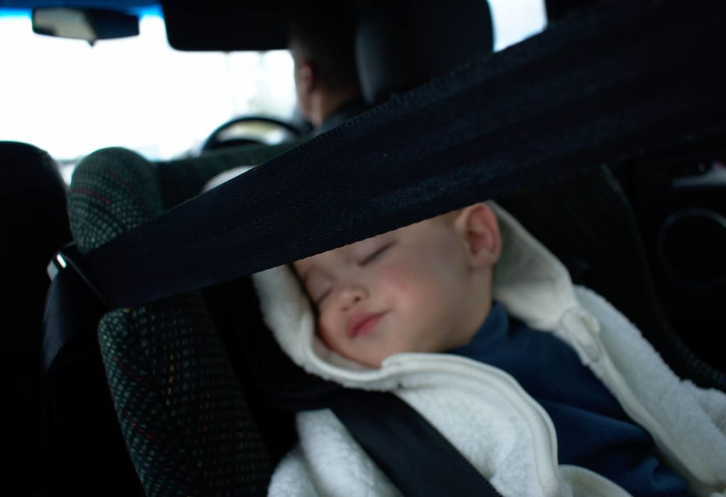 child asleep in rear-facing car seat