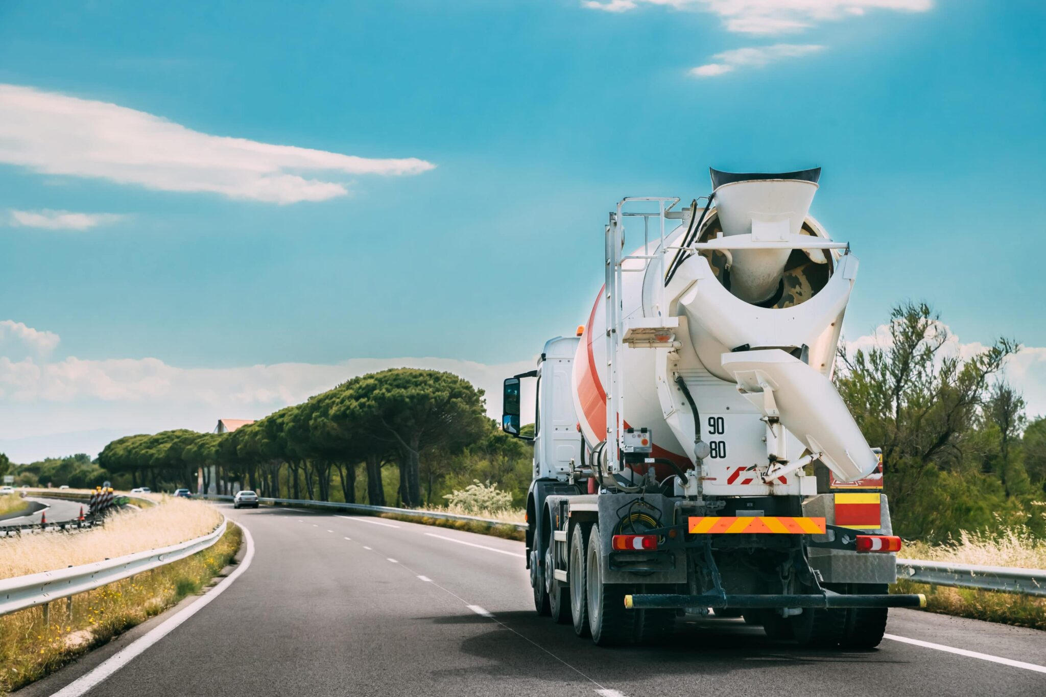 MIxer truck driving on an open road with a blue sky