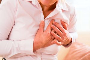 Woman suffering a heart attack holding chest