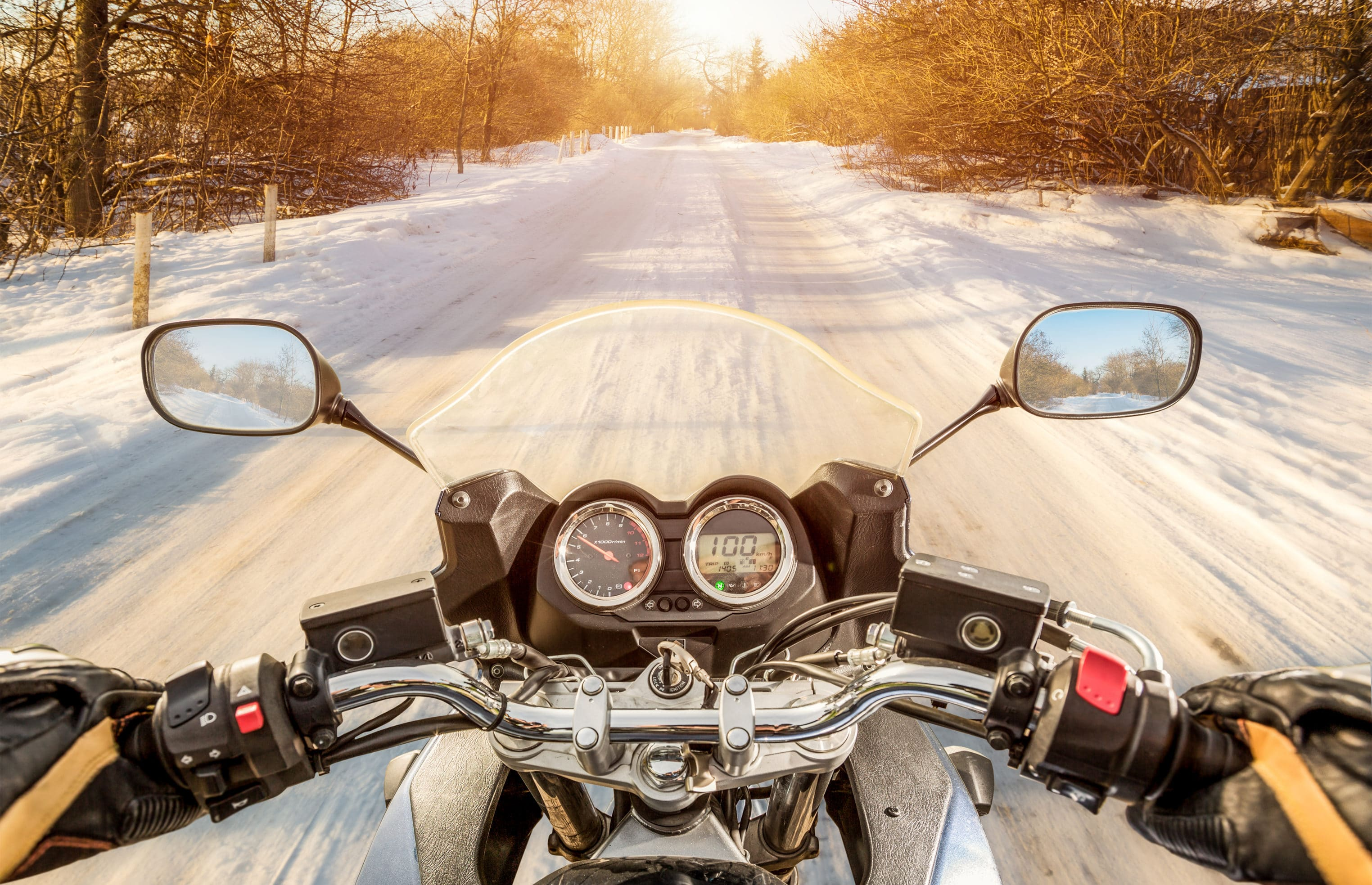 From the view of a motorcycle driver, a winter road covered in snow and the dashboard of a motorcycle.