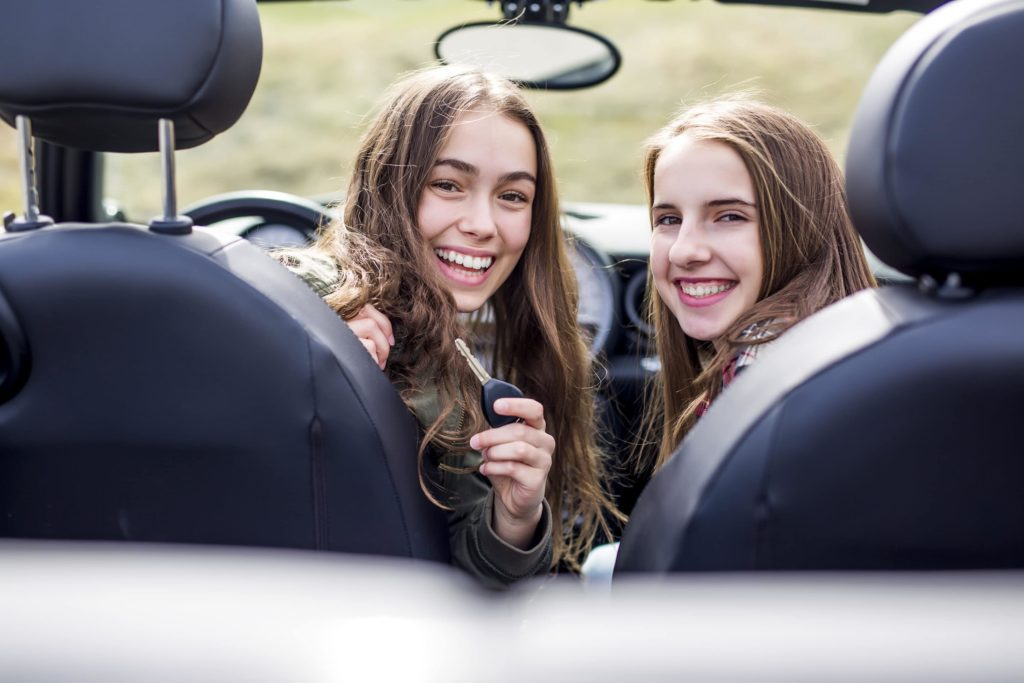 Two happy teenage girls in the driver and passenger seats showing off a set of keys