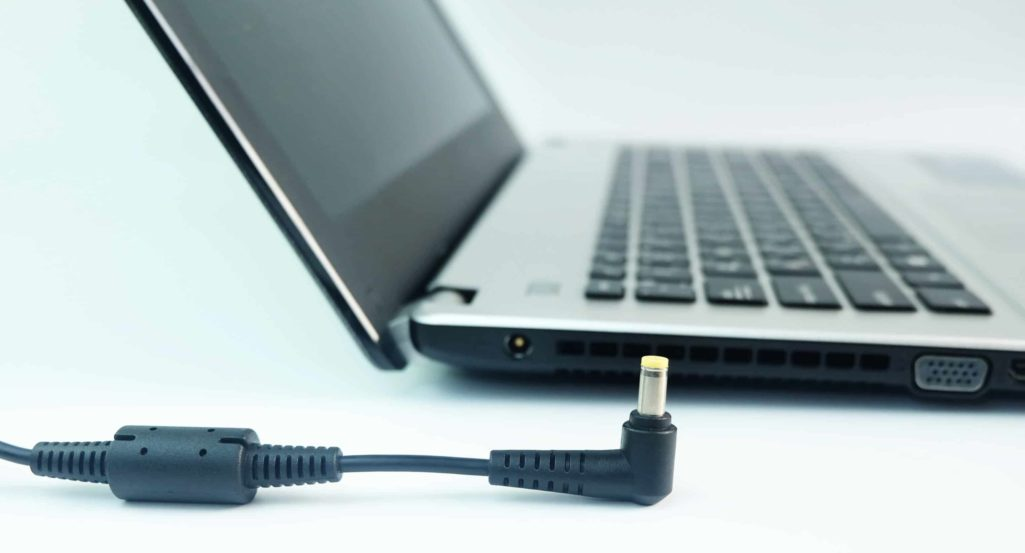 Gray and black hard-disk drive laptop with a charger left unplugged by its side