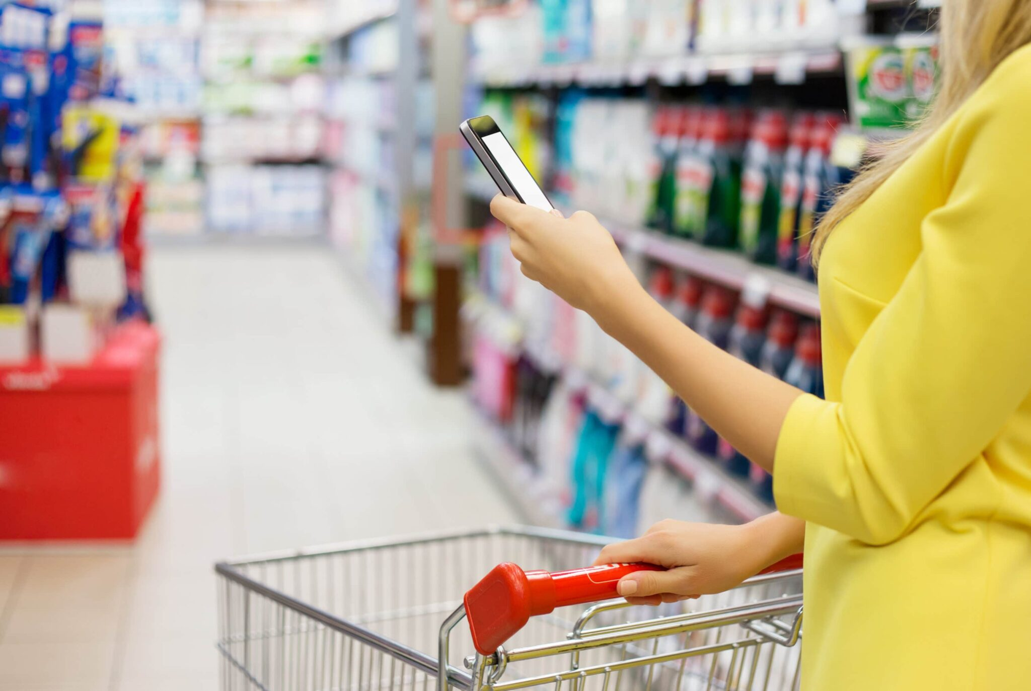 Woman in a yellow shirt looks at her phone in a deparrtment store aisle.