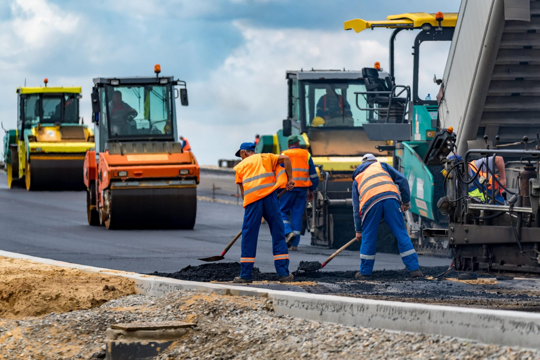 Construction workers at a roadside construction site applying pavement.