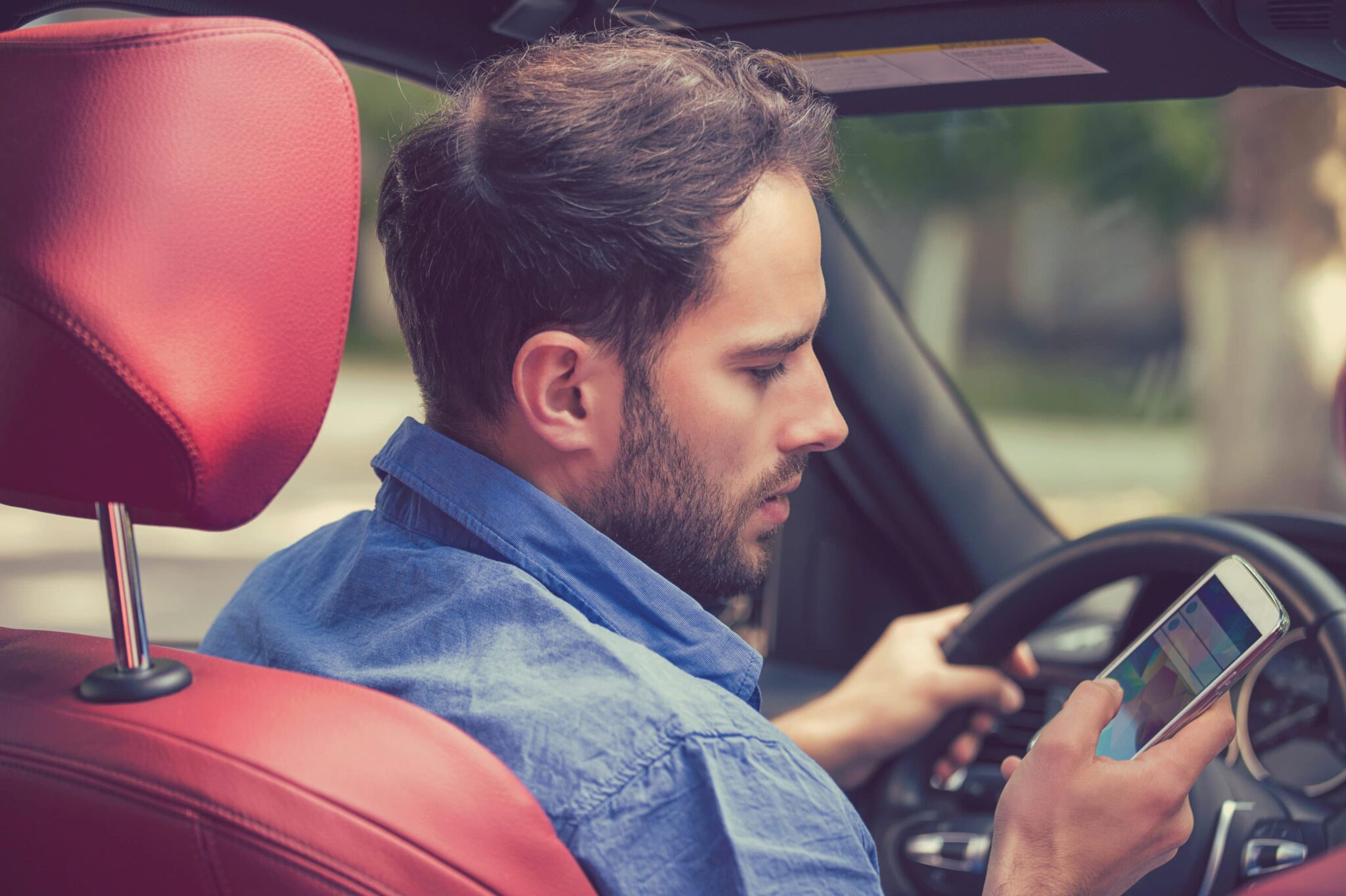 Man in the driver's seat of a car looks at his smartphone while driving.