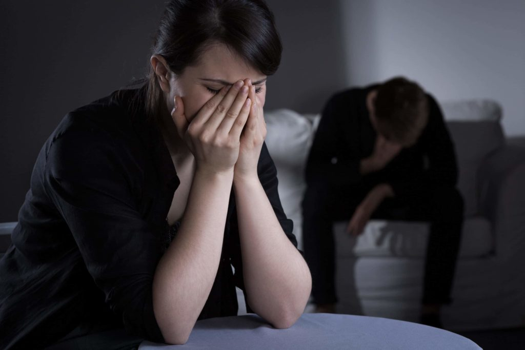 Woman and man mourning the death of a loved one in a dimly lit living room