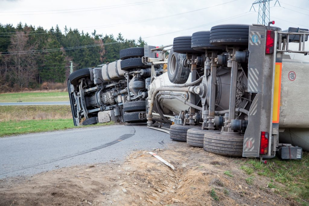 Truck is shown overturned on a highway after an accident.
