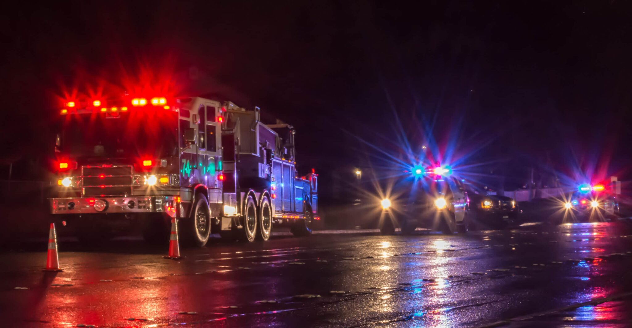 Fire trucks and emergency responder vehicles on a dar road on a rainy night.