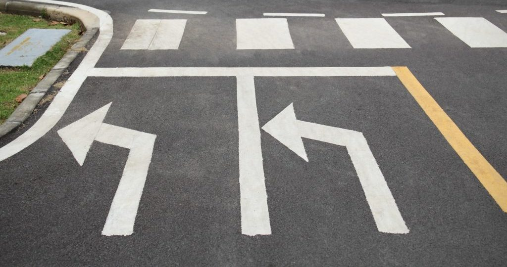 Left-turn signals drawn at an intersection in white paint