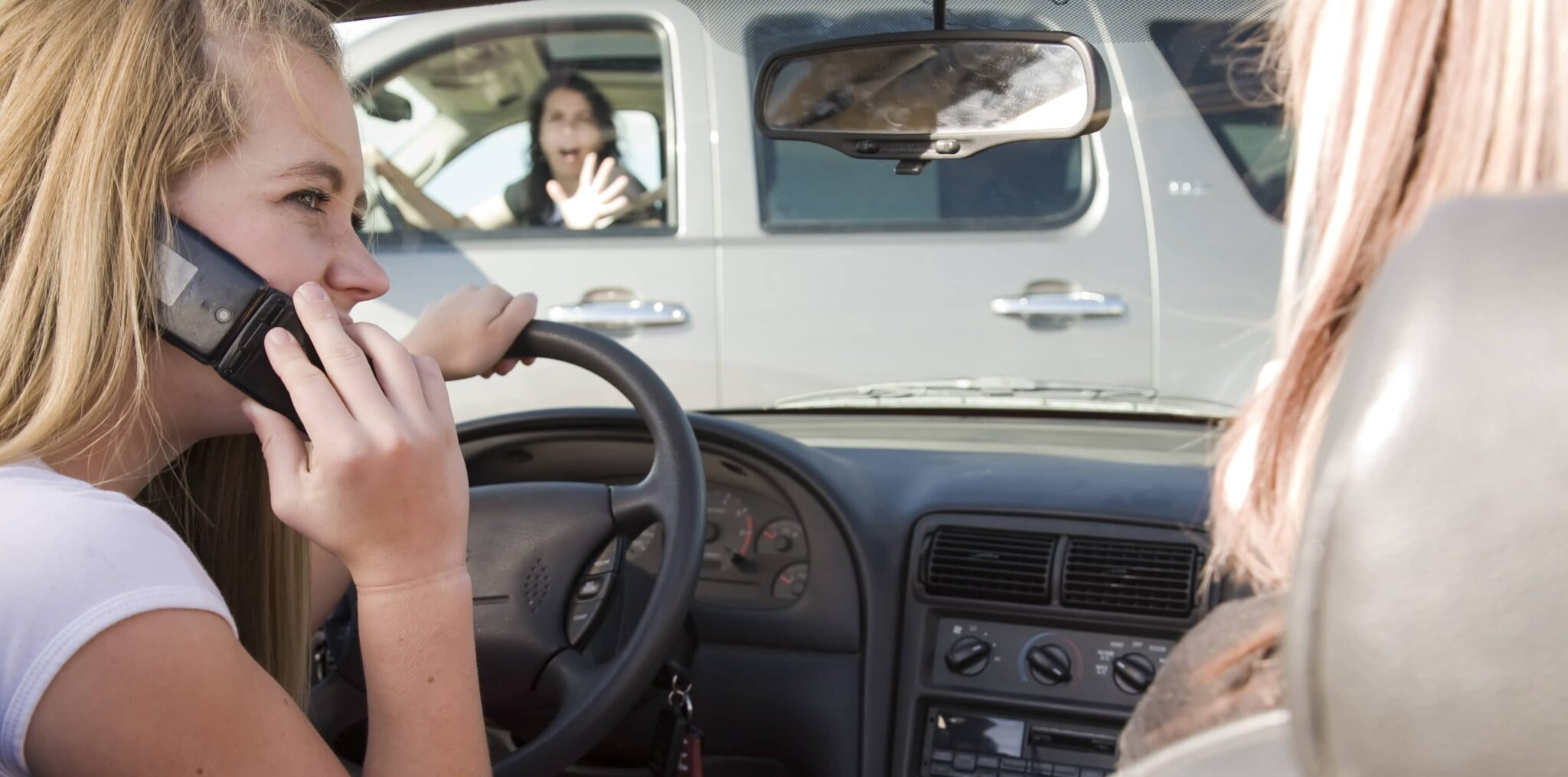 Girl talks on a phone and laughs with passenger as she dangerously approaches another driver who is in a vehicle waving her hand in front of her, fearing a collision