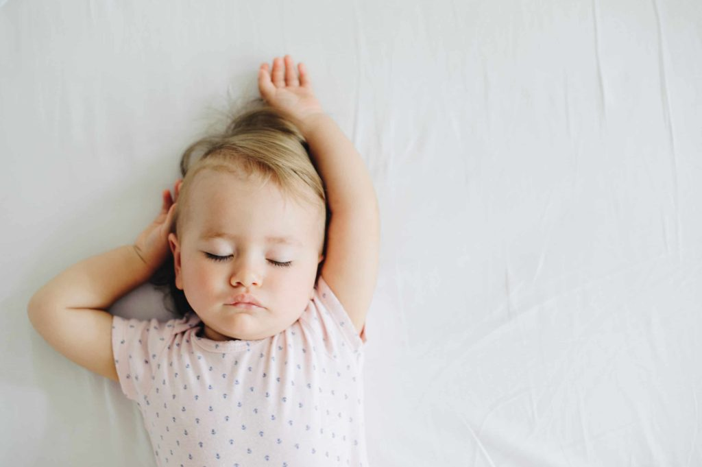 small child sleeping on a white sheet shown in aerial view