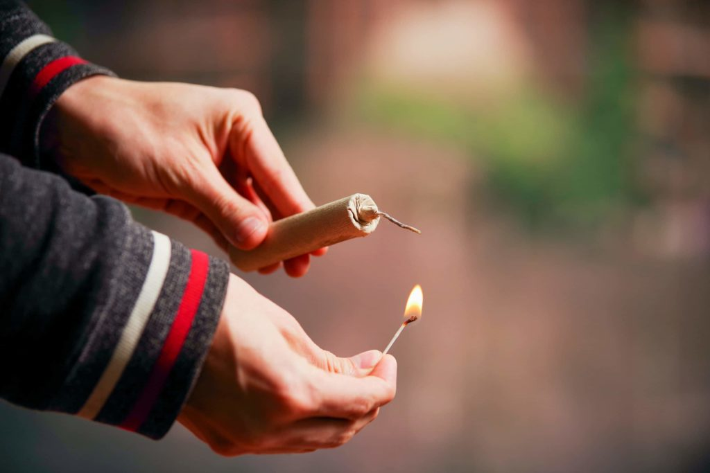 Man's hands shown lighting a small brown firewor