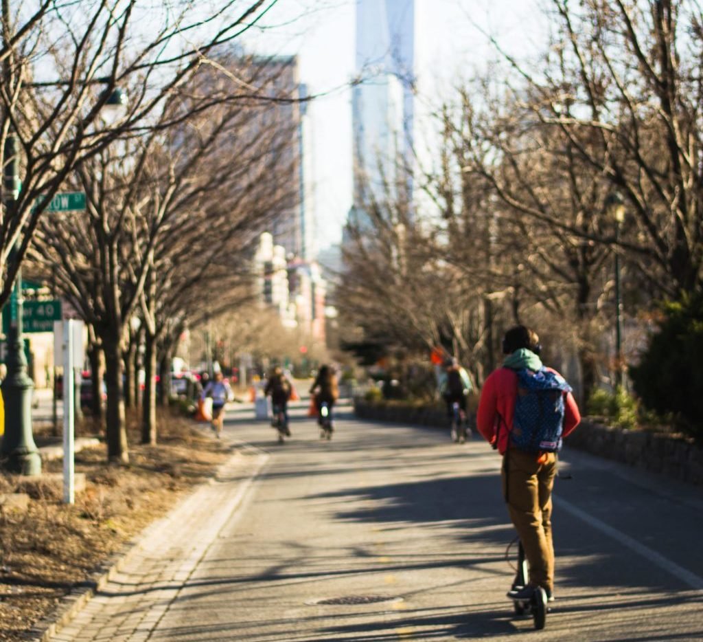Person rides on a scooter in a NYC park toward the 1 World Trade Center building shown in the background.