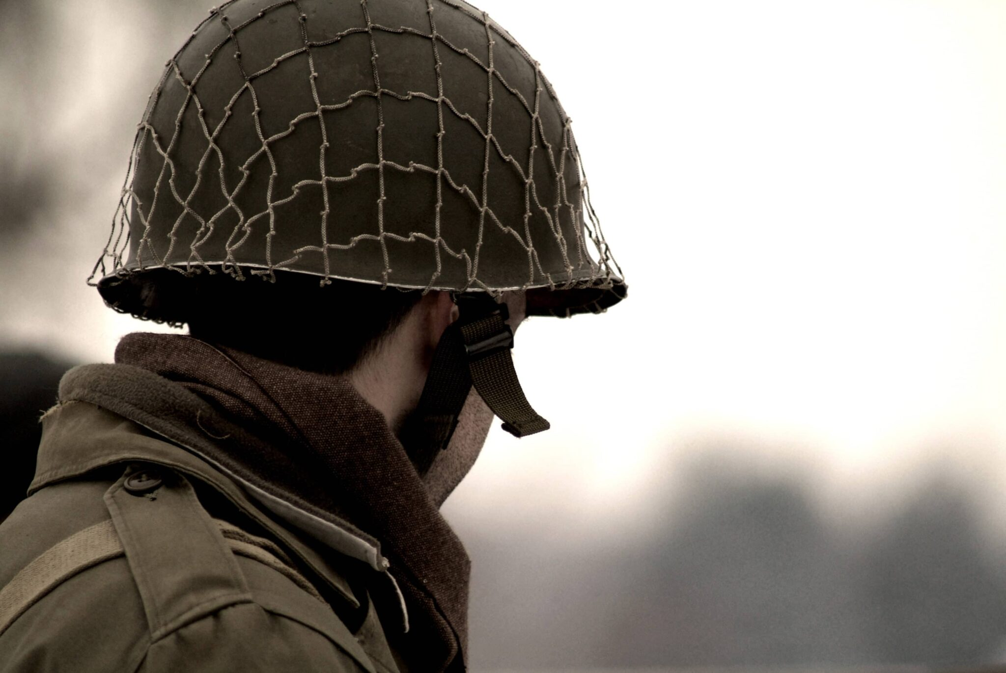 Army person with a helmet stares into a green background