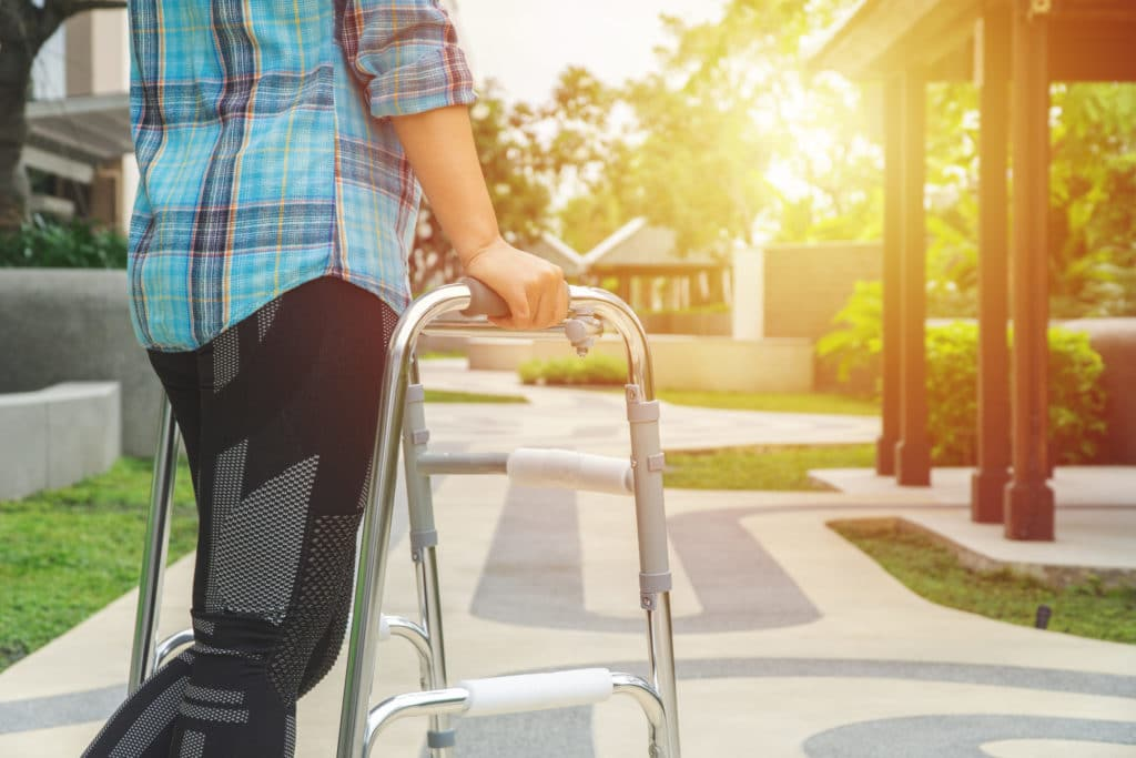 A person in a plaid shirt and athletic pants walks with an aluminum walker toward a setting sun in an outdoor courtyard.