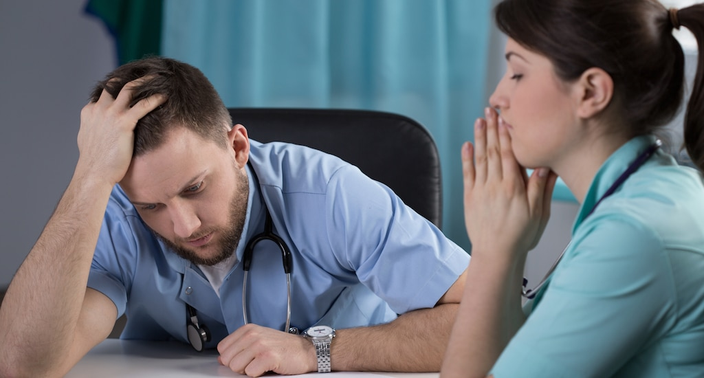 Young woman doctor closes eyes with hands to her mouth, while a young male doctor sitting next to her looks preoccupied after they both realize a medical mistake